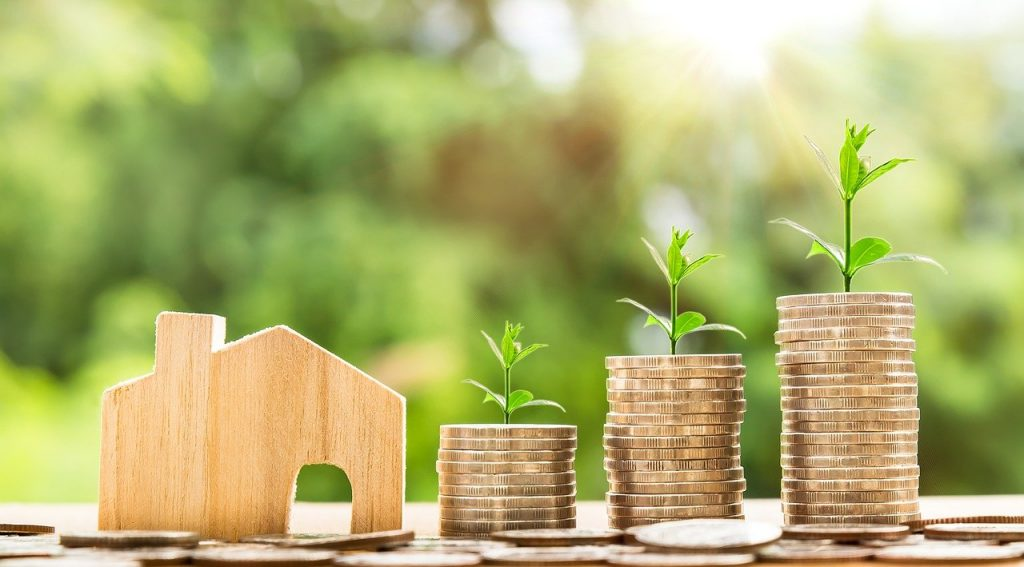 image of money pile growing with wooden house